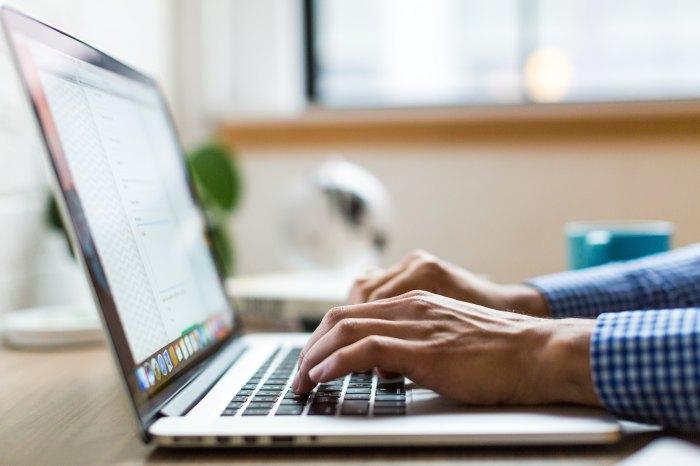 Fingers typing on laptop keyboard.