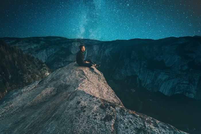 Man looking over cliff and into starry skies.