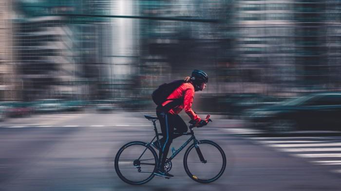 Man rushing through traffic on bike.